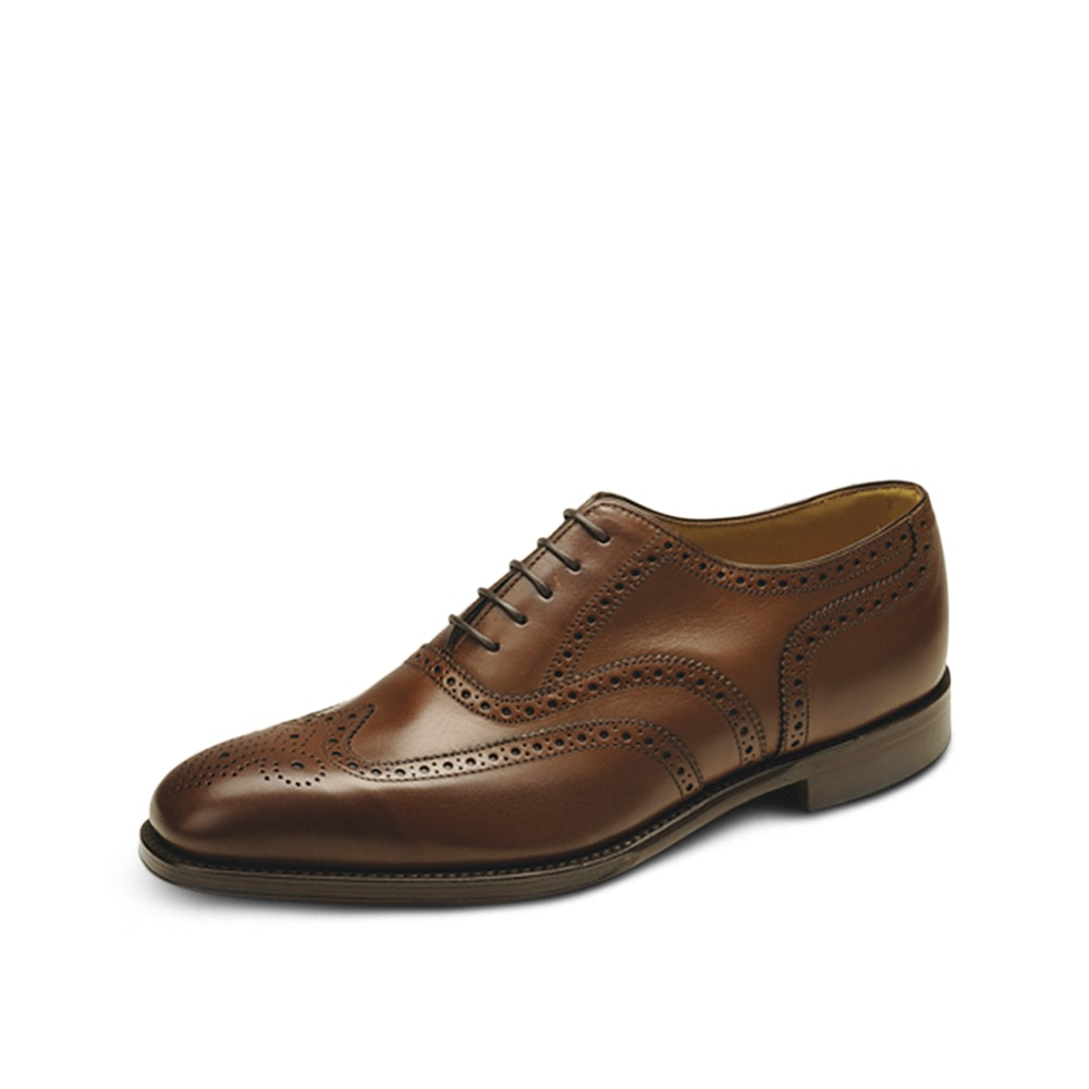 Loake 1880 Buckingham Brogue Shoes 5 Generations of Goodyear-Welted Shoes -- Among the oldest shoemakers in England, Loake is still run today--five generations after its birth--by the Loake family. Like the founders did in the 19th century, the company's craftsmen still construct each pair of shoes in their 1880 line using a Goodyear welt: a painstaking process that ensures the shoes are recraftable for years to come. And the Buckingham brogue shoes are no different. Built on the company's Capital last, these Goodyear-welted shoes feature a calfskin leather or suede upper with an understated brogued effect, along with a full leather lining, leather insole, and rubber heel tip to assist wear.