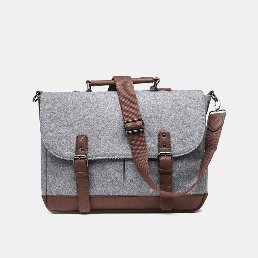 Something Strong Rebuilt Laptop Messenger Bag Wool Bag With Padded Compartment -- Large enough for your laptop, notepad, and a stack of books, the Something Strong Rebuilt messenger bag is great for days spent at the office or on campus. It features a wool exterior with your choice of tonal or contrast trim, and inside, a preppy striped lining. There's a padded compartment for your laptop or tablet, along with a pair of drop-in front pockets for your cables, pens, and other accessories. The magnetic flap-over closure keeps everything secure. Sling the bag over your shoulder or adjust the strap length and wear it cross-body. Or, remove the strap entirely and carry the bag by the handle like a briefcase.